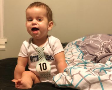 childhood development milestones and infantile-onset Pompe disease   Pompe Disease News   Author's child Cayden at 10 months old sits upright on a bed while grasping a blanket