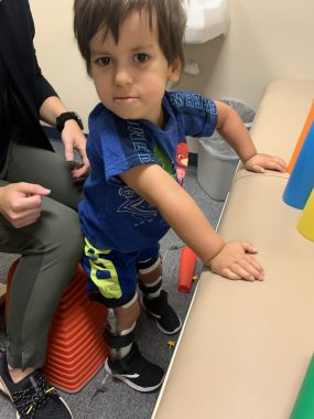 childhood development milestones and infantile-onset Pompe disease   Pompe Disease News   Author's child Cayden at age 3 standing upright with assistance from a physical therapist. Cayden is looking intently at the camera with a slight smile, a bright blue shirt, and ankle, knee, foot orthotics